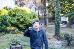 7-ти летний ребенок outdoors в саде в зиме делает большое мыло Стоковые Фото