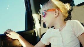 6-ти летняя девушка в солнц-защитных розовых стеклах едет в заднем сиденье автомобиля Оно прикреплено с ремнем безопасности видеоматериал