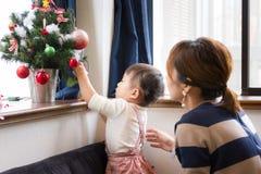 1-ти летняя девушка и мать украшая рождественскую елку стоковое фото rf