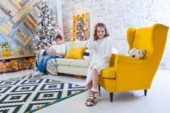 10-ти летняя девушка сидит на желтом стуле в доме перед праздниками рождества На заднем плане мальчик сидит Стоковое Изображение RF