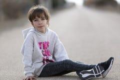 10-ти летняя девушка сидя на поле автомобиля смотря ca Стоковые Фото