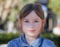 10-ти летняя девушка усмехаясь на камере, Outdoors на парке на солнечном после полудня стоковое фото rf