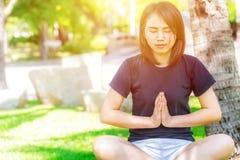 Ткань азиатской здоровой предназначенной для подростков носки вскользь делая йогу в парке стоковое фото rf