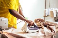 Ткань африканской белошвейки женщины утюжа Стоковое Изображение RF