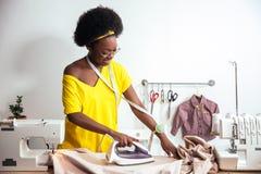 Ткань африканской белошвейки женщины утюжа Стоковое Фото