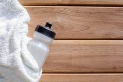 ткань взгляд сверху белые и бутылка с водой пластмассы на деревянном столе Стоковые Изображения