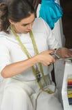 Ткань вырезывания белошвейки девушки с ножницами Стоковое фото RF