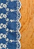 Ткань джинсов с вышивкой белого цветка клала над переклейкой стоковое фото rf