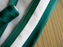 Ткань, потоки и крепежная деталь на деревянной предпосылке Стоковое Фото
