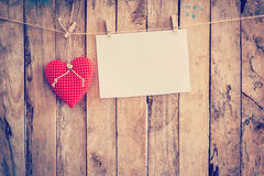 Ткань сердца и смертная казнь через повешение бумаги на веревке для белья на деревянной предпосылке Стоковое фото RF