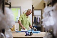 Ткань старшего человека утюжа Стоковые Фотографии RF