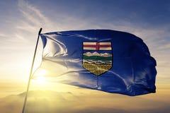 Ткань ткани ткани флага Альберты развевая на верхнем тумане тумана восхода солнца иллюстрация вектора