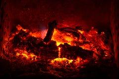 Тлеющие угли с, который сгорели журналами и золы в камине Стоковые Изображения RF