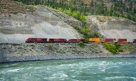Товарный состав железной дороги канадца Тихой океан двигая вдоль реки Томпсона Стоковые Фотографии RF