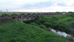 Товарный состав идет через железнодорожный мост, вечер лета сток-видео