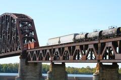 Товарный состав пересекая стальной железнодорожный мост реки ферменной конструкции стоковая фотография rf
