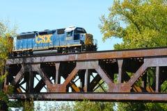 Товарный состав пересекая стальной железнодорожный мост реки ферменной конструкции стоковые изображения rf