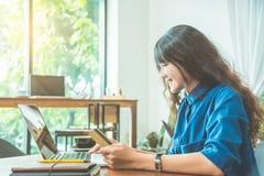 Товары женщины покупая онлайн через портативный компьютер стоковые фотографии rf