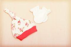 Товары младенца Одежда ` s детей, шляпа с цветками и белые перчатки на предпосылке изменяя таблицы Стоковое Изображение RF