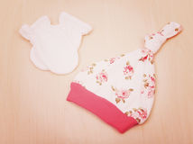 Товары младенца Одежда ` s детей, шляпа с цветками и белые перчатки на предпосылке изменяя таблицы Стоковые Изображения RF