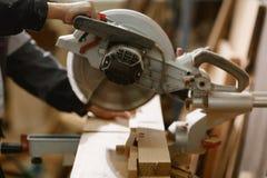 Токарный станок с острым круглым ножом за которым мужской плотник работает Стоковая Фотография RF