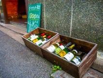 ТОКИО, ЯПОНИЯ -28 ИЮНЬ 2017: Сортированные пустые botles вина внутри деревянной коробки, размещенный на том основании в dowtown в Стоковое Изображение