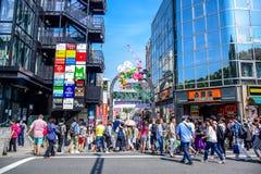 ТОКИО, ЯПОНИЯ: Люди ходят по магазинам на улице Takeshita, известной торговой улице выровнянной с магазинами модной одежды, кафам Стоковое фото RF