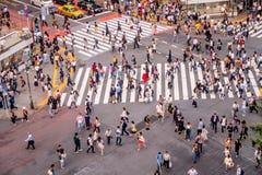 ТОКИО, ЯПОНИЯ 28-ОЕ ИЮНЯ - 2017: Взгляд сверху толпы людей пересекая в улицу Shibuya, один из самых занятых crosswalks внутри Стоковые Фотографии RF