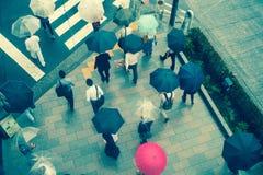 ТОКИО, ЯПОНИЯ 28-ОЕ ИЮНЯ - 2017: Вид с воздуха неопознанных людей под зонтиками на улице скрещивания зебры в Jimbocho Стоковое Фото