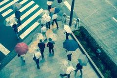 ТОКИО, ЯПОНИЯ 28-ОЕ ИЮНЯ - 2017: Вид с воздуха неопознанных людей под зонтиками на улице скрещивания зебры в Jimbocho Стоковая Фотография RF