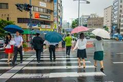 ТОКИО, ЯПОНИЯ 28-ОЕ ИЮНЯ - 2017: Неопознанные люди под зонтиками на улице скрещивания зебры в обнаруженном местонахождение районе Стоковые Изображения