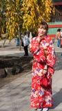 ТОКИО, ЯПОНИЯ - 31-ОЕ ОКТЯБРЯ 2017: Гейша в красном кимоно на улице города вертикально Стоковое Изображение