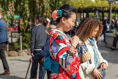ТОКИО, ЯПОНИЯ - 31-ОЕ ОКТЯБРЯ 2017: Девушка в красном кимоно на улице города Конец-вверх Стоковая Фотография