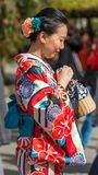 ТОКИО, ЯПОНИЯ - 31-ОЕ ОКТЯБРЯ 2017: Девушка в красном кимоно на улице города Конец-вверх вертикально Стоковое Фото