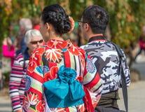 ТОКИО, ЯПОНИЯ - 31-ОЕ ОКТЯБРЯ 2017: Девушка в красном кимоно на улице города Конец-вверх задний взгляд Стоковые Фото