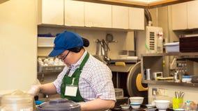 ТОКИО, ЯПОНИЯ - 31-ОЕ ОКТЯБРЯ 2017: Кашевар в кухне варит Скопируйте космос для текста стоковая фотография rf