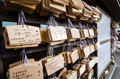 ТОКИО, ЯПОНИЯ - 23-ЬЕ НОЯБРЯ 2013: Металлические пластинкы Ema таблетки деревянные молитве на святыне Meiji Jingu Стоковая Фотография RF