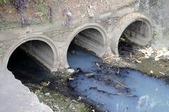 Токсическая вода бежать от сточных труб в пакостной подземной сточной трубе для драгируя чистки тоннеля стока Стоковое Фото