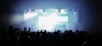 Толпа вентиляторов с руками в воздухе наблюдая концерт рок-группы Вентиляторы на перспективе точки зрения концерта стоковые фото