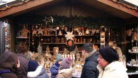 Толпа Европа в декабре людей девушки деревянного стойла рождественской ярмарки усмехаясь акции видеоматериалы