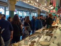 Толпа идя сырцовыми морепродуктами на льде на открытом рынке места Pike стоковое изображение