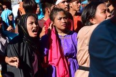 Толпа кричать людей и женщин маршируя, chanting создающ тревогу на улице Стоковое Фото