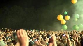 Толпа людей играя с большими шариками на рок-концерте на ноче, зеленом освещении видеоматериал