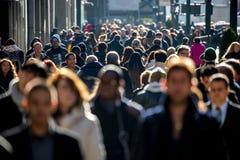 Толпа людей идя на тротуар улицы