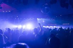Толпа людей partying в клубе диско, свете и лазерах и туманной окружающей среде стоковые фотографии rf