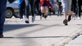 Толпа ног бегунов людей и спортсменов бежит вдоль дороги в городе акции видеоматериалы