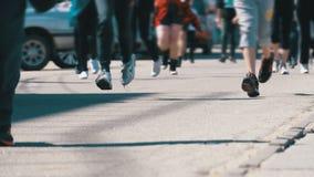 Толпа ног бегунов людей и спортсменов бежит вдоль дороги в городе сток-видео