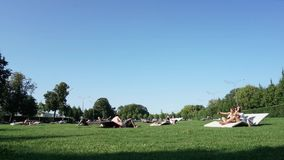 Толпа рискованного предприятия непознаваемая людей наслаждаясь летом сидя на траве в парке акции видеоматериалы