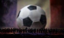 Толпа силуэта на большом запачканном футбольном мяче принципиальная схема творческая Стоковое Фото