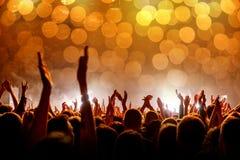 Толпа с поднятыми руками на концерте, светлом шоу стоковая фотография
